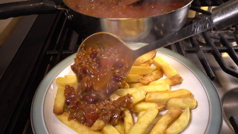 Close shot of hot beef chilli con carne being served from a cooking pan sitting on a hob, over to a plate of oven baked chips / fries.