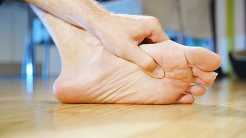 Massaging painful foot by hand slow motion 4K. Low angle long shot of person's foot in focus while massaging with a hand at home. Background dining room out of focus.