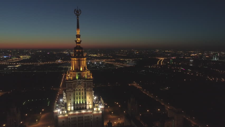 Illuminated Moscow State University and Cityscape in Morning Twilight. Russia. Aerial View. Drone is Flying Forward and Upward and Approaching to Spire | Shutterstock HD Video #1011688898