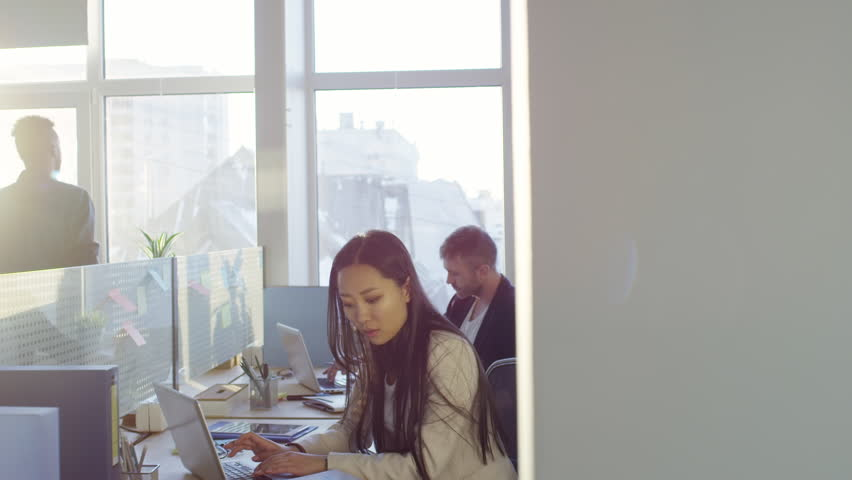 Tilt down shot of young Asian businesswoman typing on laptop and reading document at desk in modern open space office; colleagues working in background | Shutterstock HD Video #1011700058