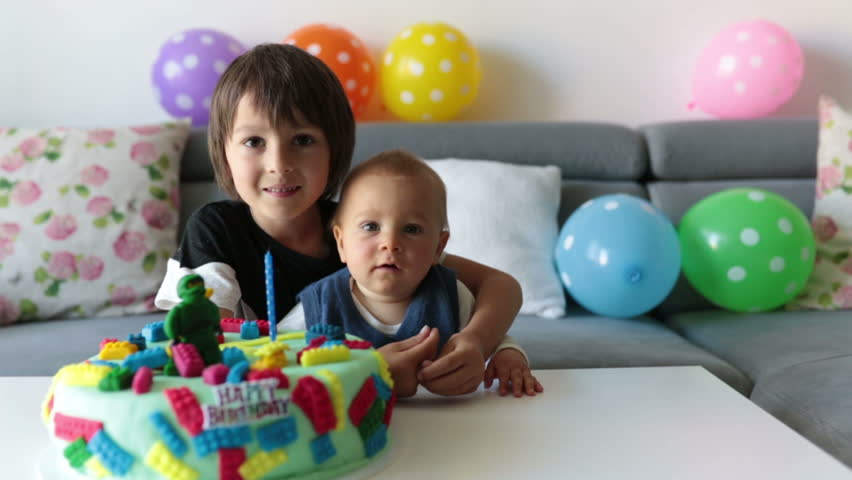 Cute children, boy brothers, celebrating birthday with colorful cake, candles, balloons at home  | Shutterstock HD Video #1011702758