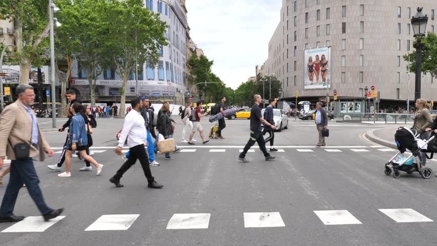 Barcelona, Spain - May 14, 2018: People crossing a road next to La Rambla famous street , downtown Barcelona.