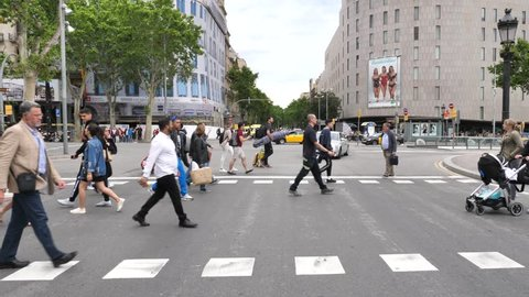 Barcelona, Spain - May 14, 2018: People crossing a road next to La Rambla famous street , downtown Barcelona.