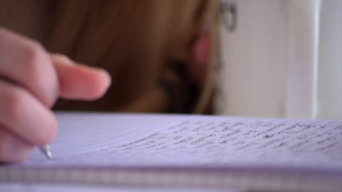 A low angle close up pull focus shot of a student making notes to study.