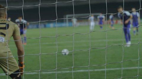 Proffesional football soccer game. Defocused footballer scoring a goal, 75 fps slow motion