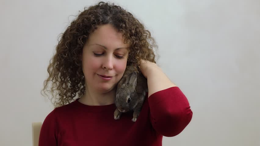 Woman fondles dwarf rabbit which lies on her shoulder, at white background