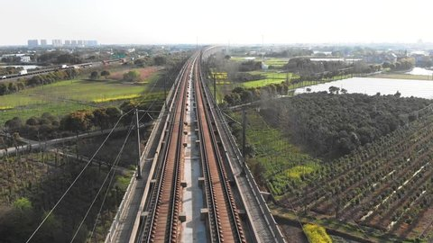Raised high speed rail train passes. China's bullet train zooming through the rural countryside. Drone shot of moving gaotie on elevated railway.