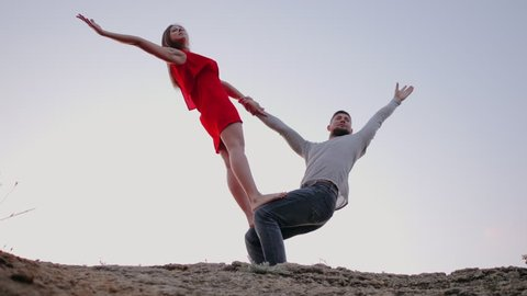 Man and woman practicing yoga together outdoors. Girl in red dress, boy in casual style clothing. Beautiful couple doing acro-yoga on the beach at sunrise, slow motion