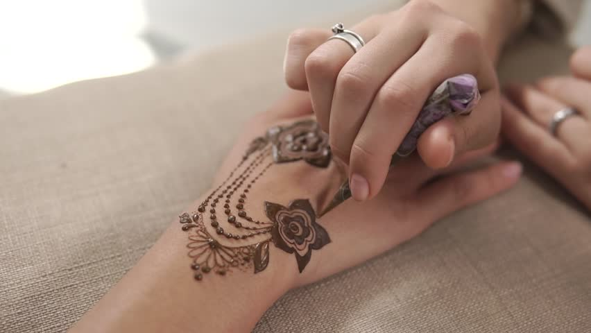 Master is performing mehndi beauty treatments in studio. Woman is decorating hands of client girl by temporary henna tattoos