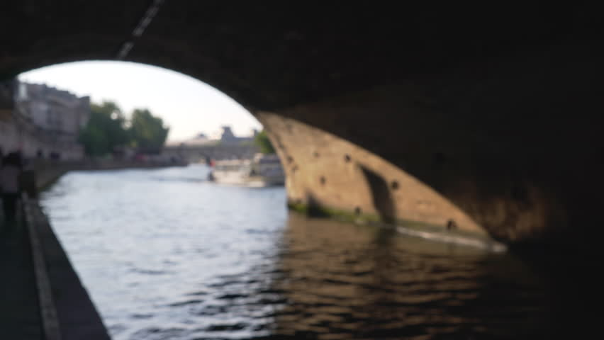 Dynamic perspective of the Seine River flowing through underpass in Paris. Arch ceiling tunnel above boy of water in France | Shutterstock HD Video #1011784688