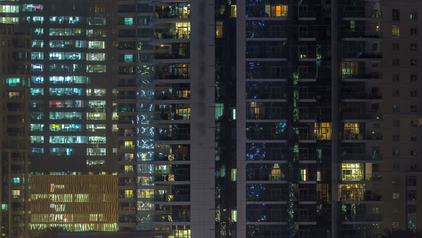 Glowing windows of skyscrapers at night timelapse. View of modern residential and office high-rise buildings in Dubai marina. People moving inside. Aerial top view. Zoom in #1011785348