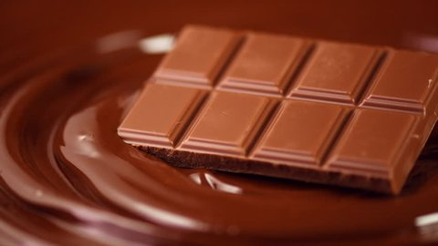 Chocolate bar rotated over melted dark chocolate swirl liquid background. Confectionery concept backdrop. Sweet dessert. 4K UHD video, slow motion