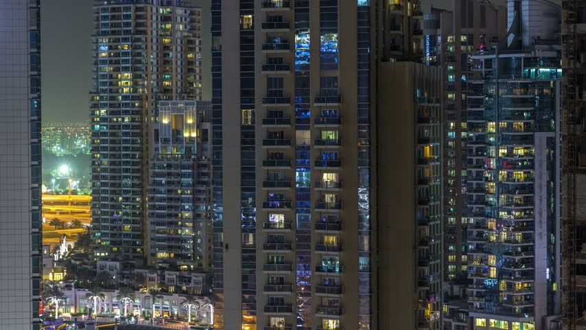 Residential towers with lighting and illumination timelapse. Road and promenade on Dubai Marina and JLT skyline at night. Traffic near skyscrapers with glowing windows | Shutterstock HD Video #1011839708