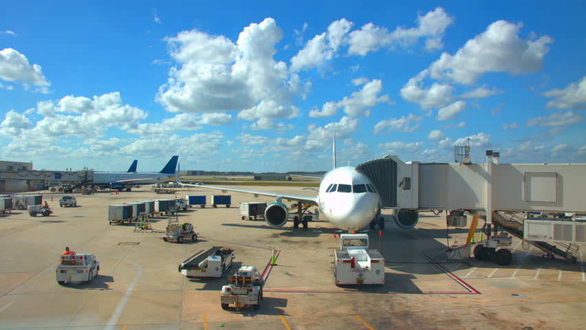 Generic Airport Concourse Exterior with Parked Airliners with Ground Support Vehicles Driving Around on a Sunny Day with White Clouds in a Blue Sky