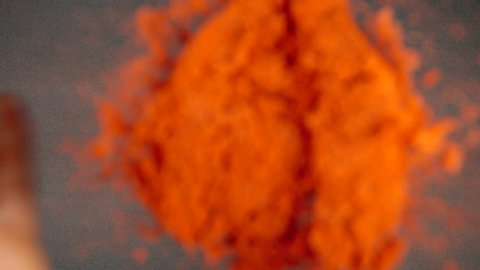 TOP VIEW: Red pepper powder falling and splashing on a black table - Slow Motion