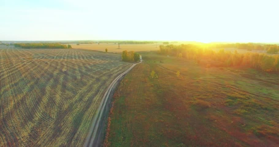UHD 4K aerial view. Mid-air flight over rural dirt road with car. Yellow rural field at sunny autumn evening. Green trees on horizon. Horizontal movement. | Shutterstock HD Video #1011858878