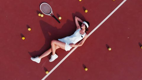 OVERHEAD DRONE shot of young Caucasian teen model wearing fashionable tennis dress, lying on tennis hardcourt with a lot of balls, summer sunny day outdoors. Fashion portrait shoot