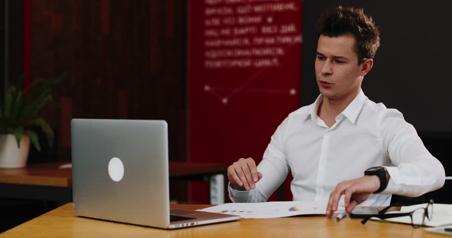 Man talks on the video-call on his laptop in the office. Young attractive businessman in a white shirt showing fuck you o after the video call