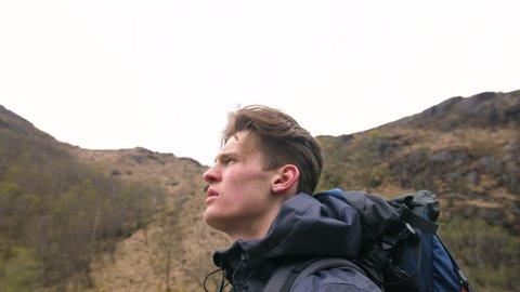 4K close up side profile of handsome traveller looking into the distance in Scottish Highlands.Trekker man  hiking through Scotland UK.