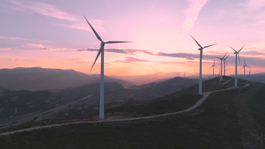 Wind turbine farm on beautiful purple evening mountain landscape. Renewable energy production for green ecological world. Aerial view of wind mills farm park on evening mountain. Lateral flight #1011896708