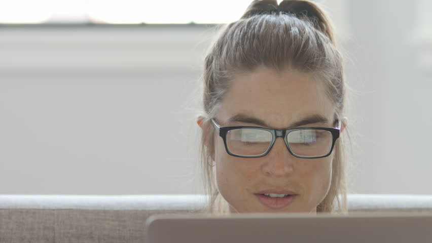 An attractive woman working on her computer on a couch, 4K slow motion | Shutterstock HD Video #1011898838
