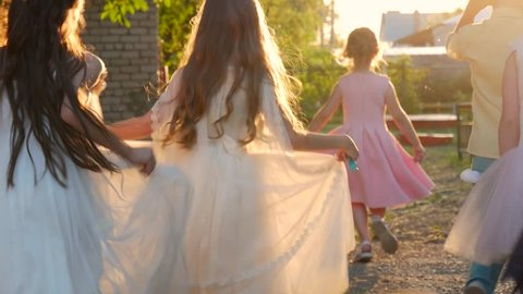 Beautiful little girls in princess dresses run away at sunset.