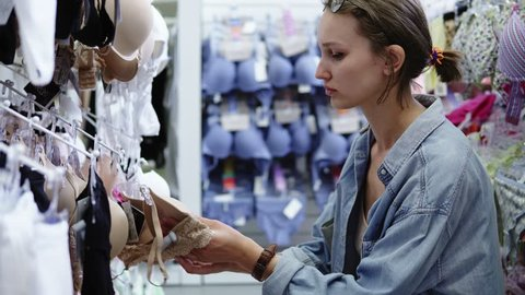 Woman with short hair in casual shopping in mall. Looking for perfect lingerie. Choosing underwear, bra. Side view