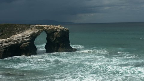 Long shot of stunning arched cliffs and waves. Arched cliff at Costas do Catedrais in Galizia, Spain