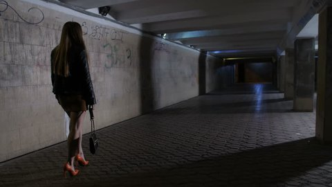 Drunk boozy female in mini skirt and high heeled shoes walking alone in dark underpass tunnel alone. Tipsy woman stumbling and touching the wall trying to find the way home at night