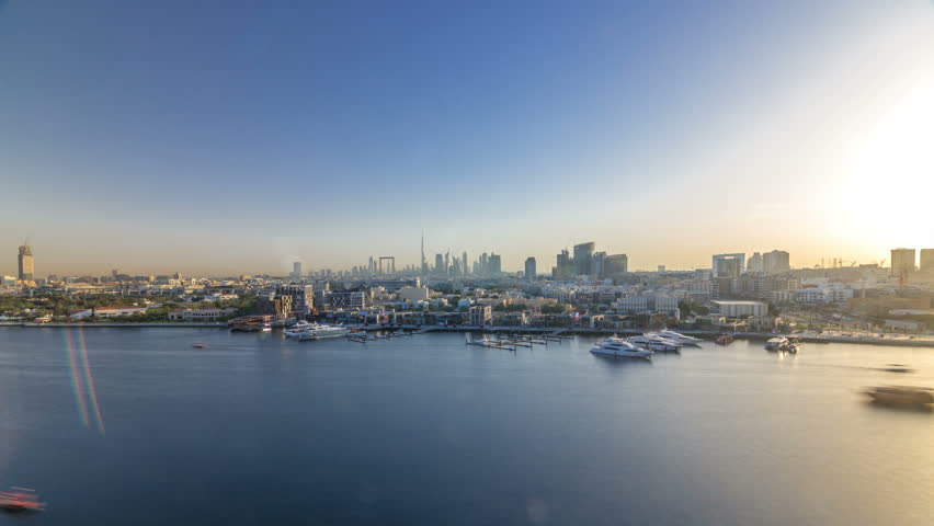 Dubai creek landscape timelapse with boats and ship, calm water and modern buildings with downtown skyscrapers in the background during sunset. Aerial top view from above