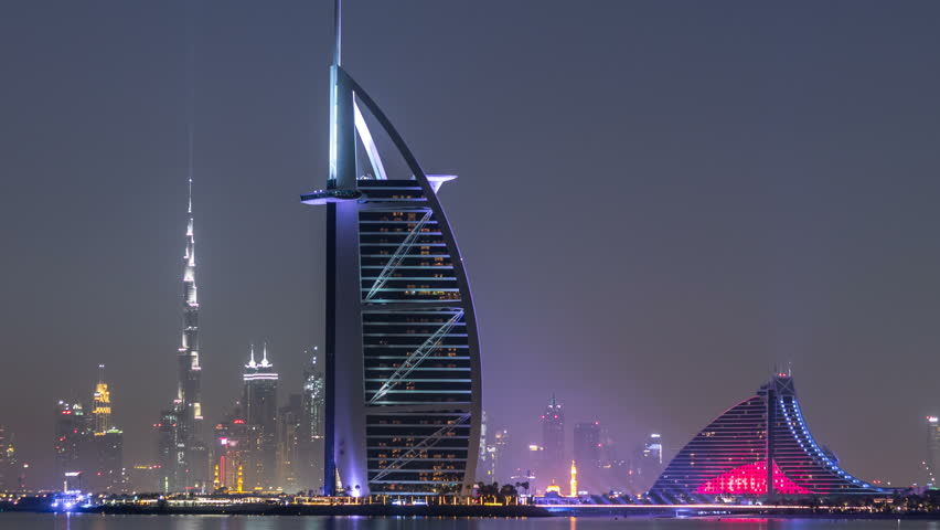 Skyline of Dubai by night with Burj Al Arab from the Palm Jumeirah timelapse. Illuminated skyscrapers reflected in water