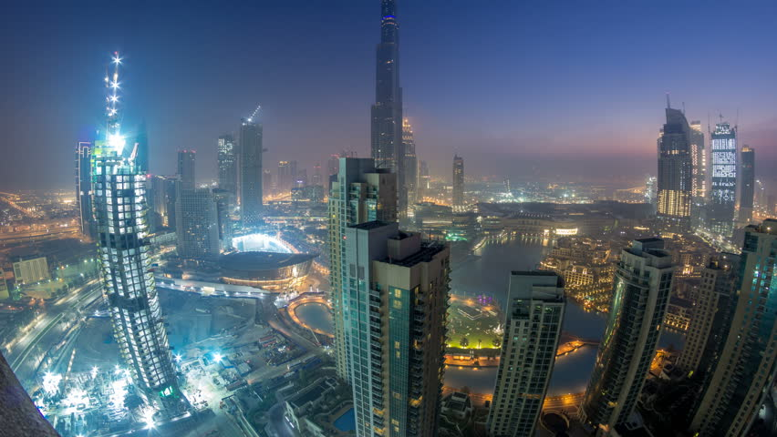 Foggy morning in downtown of Dubai night to day transition timelapse. Futuristic view of the city skyscrapers covered in mist and fountains. Aerial view from rooftop with sunrise. Dubai, UAE #1011990398