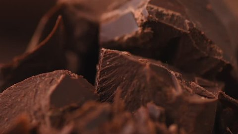 Chocolate, Chunks of sweet dark chocolate rotated, close-up. Gourmet dessert ingredient. Confectionery, confection concept. Slow motion 4K UHD video