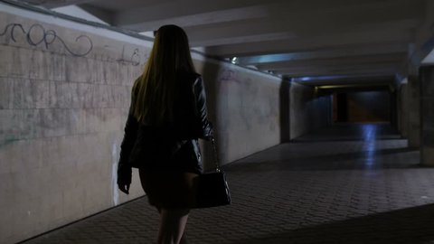 Back view of woman walking alone in subway passage at night. Man in hoodie steals bag from female's hand. Frustrated girl trying to chase robber. Upset woman gesturing with frustration. Steadicam