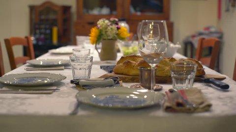 Friday evening Jewish Shabbat dinner table, holy Challah bread, shallow DOF
