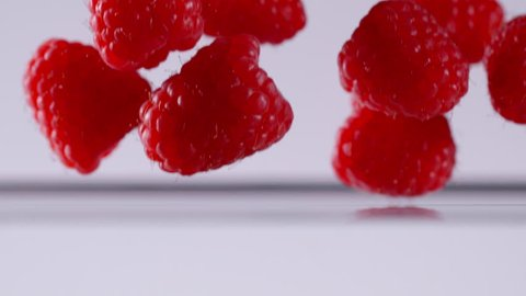 Super slow motion of falling raspberries into water. Filmed on cinema slow motion camera, 1000fps, ProRes 422 HQ codec.
