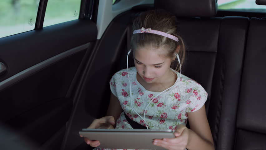 Joyful cute elementary girl in headphones playing online game with digital tablet while sitting in the back seat of car during summer road trip. Happy kid enjoying leisure with tablet pc in automobile