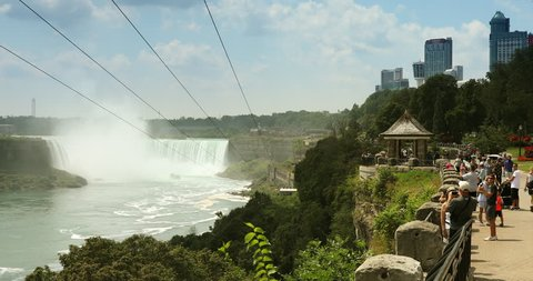 Niagara Falls, Canada - July 25, 2017:   Tourists zip line over the crowds of summer vacation tourists walking by the landmark Horseshoe Falls in Niagara Falls Ontario Canada
