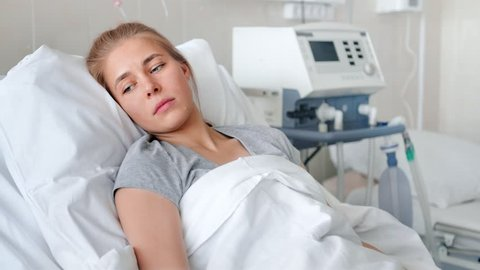 A sick young woman lying in a hospital bed and waiting a doctor