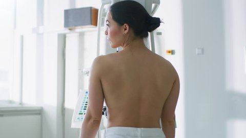 In the Hospital, Topless Female Patient Undergoes Mammogram Screening Procedure. Healthy Young Female Does Cancer Preventive Scan. Modern Hospital with High Tech Machines. Shot on RED EPIC-W 8K Camera