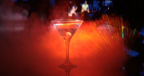 Slider shot. Glass with martini with olive inside. Close up view of glass with club drink on dark foggy toned background. Selective focus.