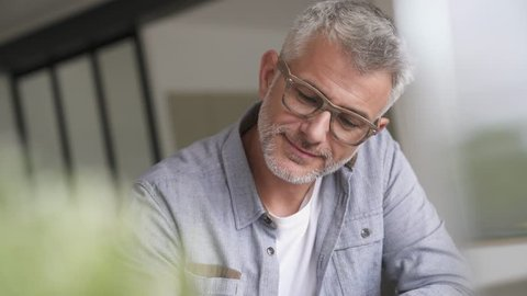 Middle-aged guy with trendy eyeglasses relaxing at home