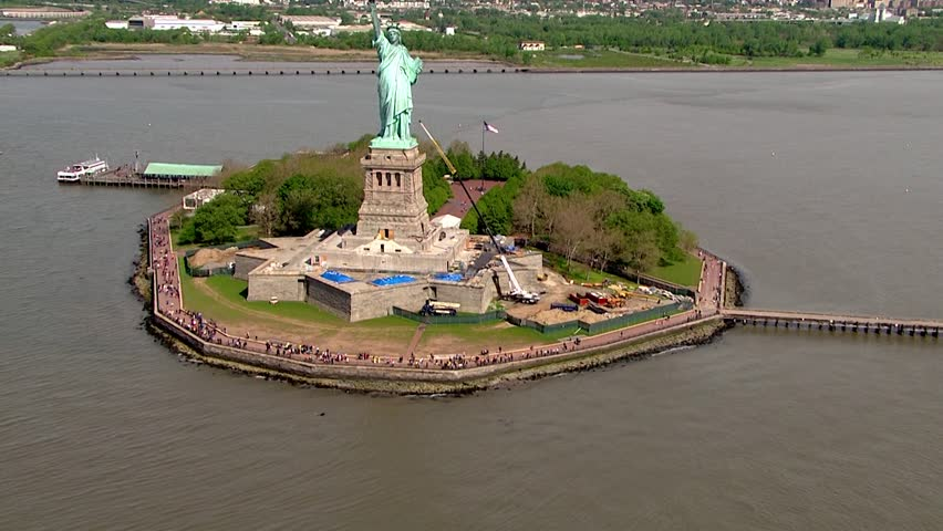 Aerial day time establishing shot tracking river water to reveal Statue of Liberty standing tall over majestic view of New York Harbor. Verrazzano Bridge and Staten Island in beautiful distance | Shutterstock HD Video #1012073888