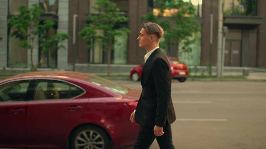 Successful young businessman walk down the street, caucasian man walking along the road outdoors. attractive guy wearing formal suit | Shutterstock HD Video #1012093628