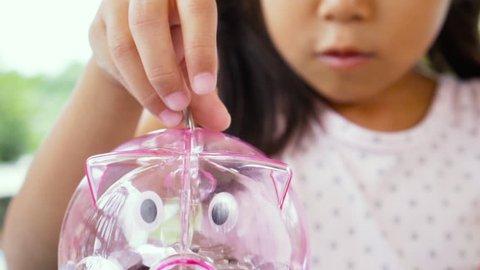 Asian little girl putting coin into piggy bank