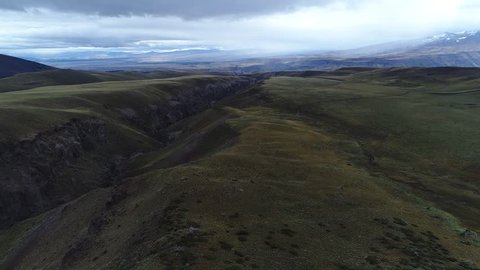 Grasslands in high altiplain of Domuyo Volcano surroundings, Covunco valley besides. Aerial drone scene moving fowards and descending next to the floor. Mountains at backgound. Neuquen, Patagonia