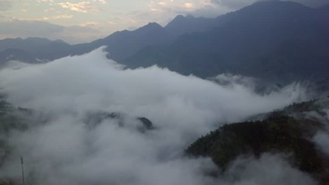 Aerial View. Flying over the high mountains in beautiful clouds . Aerial camera shot. Air clouds, Fansipan, Sapa, Vietnam.