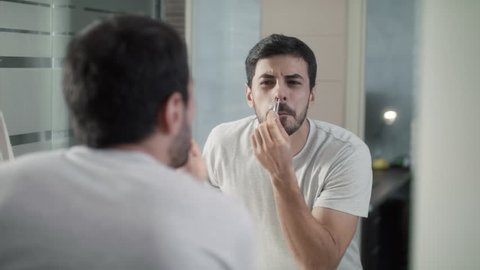 Young hispanic people and male beauty. Latino person with beard grooming in bathroom. Metrosexual man feeling pain when trimming nose hair with tweezers