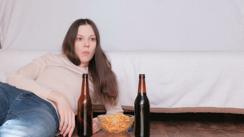 Couple of young man and woman eating chips drinking beer and watching TV.