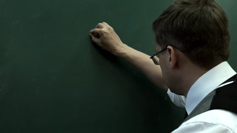 401K. The man in glasses writes on the blackboard